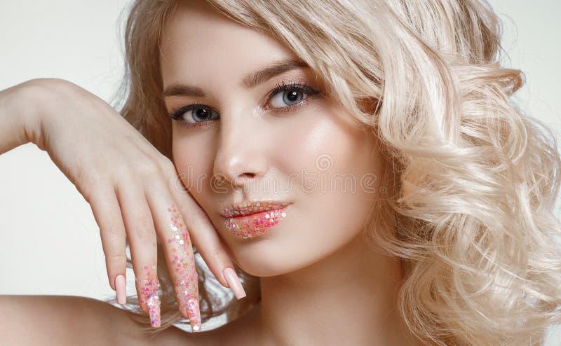 Portrait en gros plan de belle femme blondy bouclée avec le maquillage parfait d'art, conception givrée à la mode de clou avec le photos stock