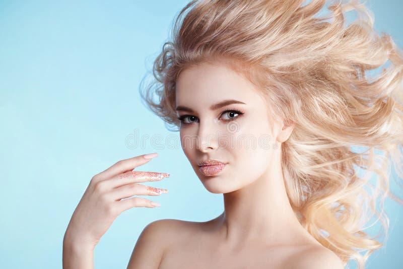 Portrait en gros plan de belle femme blondy bouclée avec le maquillage parfait d'art, conception givrée à la mode de clou avec le photo stock