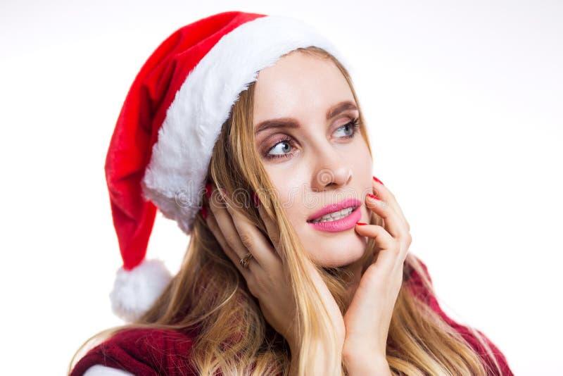 Portrait en gros plan de belle femme de Santa dans le chapeau sur le fond blanc La fille rêve et pense environ un cadeau pendant  photos stock