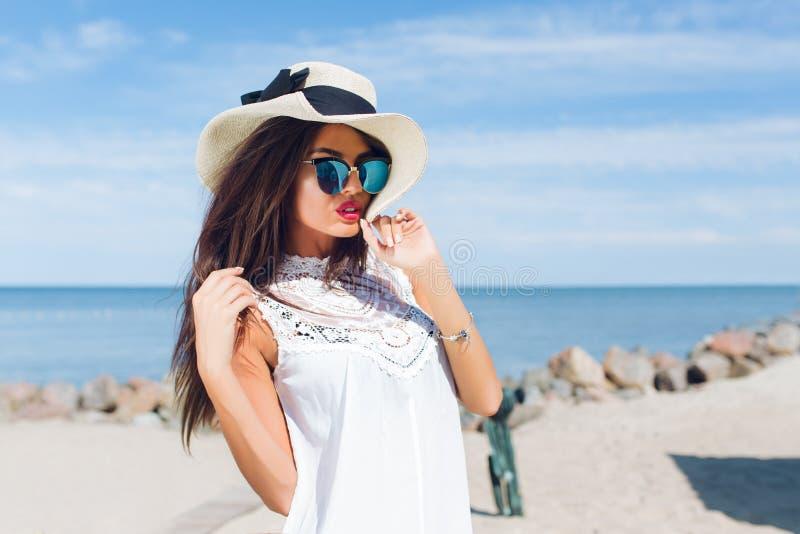 Portrait en gros plan de fille attirante de brune avec de longs cheveux se tenant sur la plage près de la mer Elle utilise le cha image libre de droits