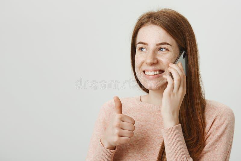 Portrait en gros plan de fille attirante de gingembre avec les taches de rousseur mignonnes parlant du téléphone portable tout en images libres de droits