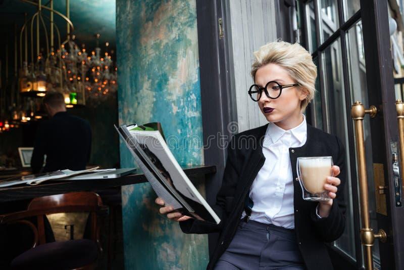 Portrait en gros plan de fille se reposant en café avec la magazine photos stock