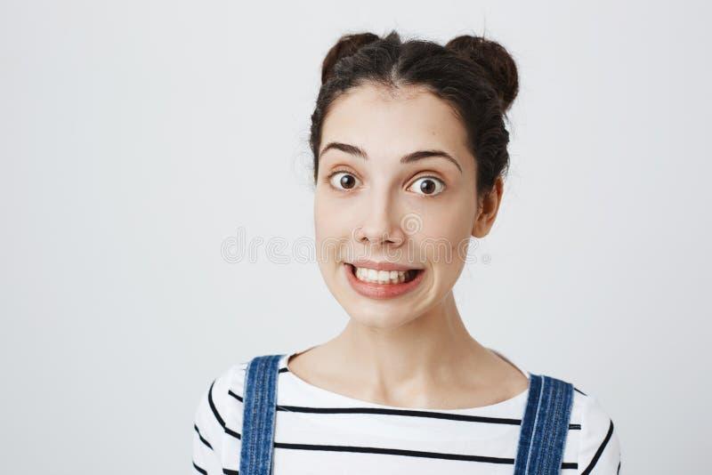 Portrait en gros plan de jeune beau modèle femelle avec la coiffure de deux petits pains, étirant la bouche dans le sourire et la image libre de droits
