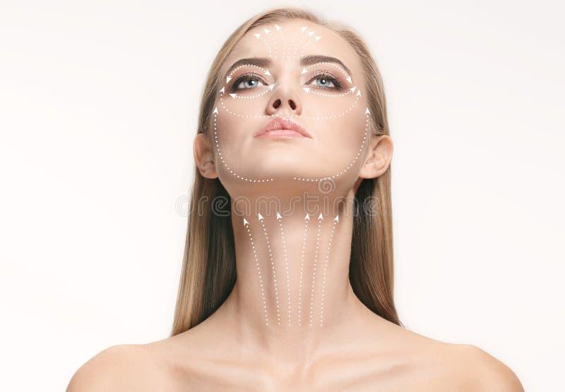 Portrait en gros plan de jeune, belle et en bonne santé femme avec des flèches sur son visage photos stock