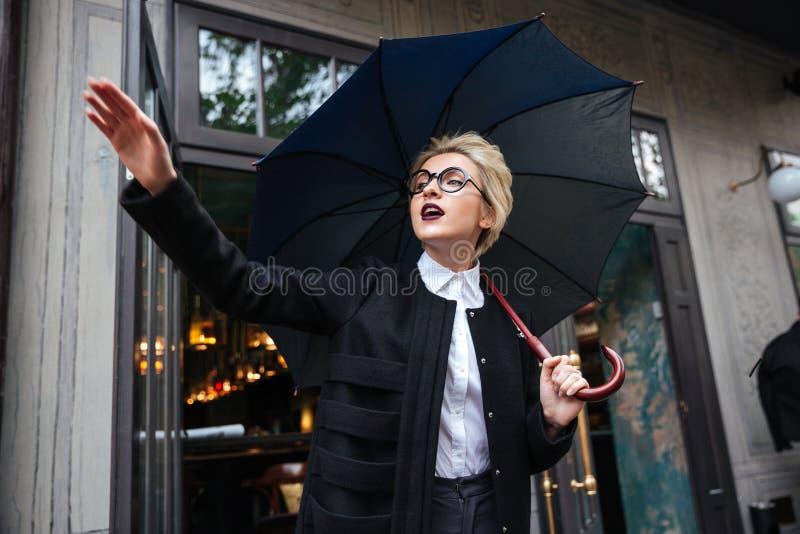 Portrait en gros plan de jeune belle femme avec l'ondulation de parapluie photographie stock