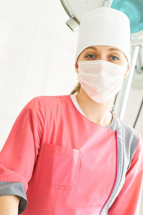 Portrait en gros plan de jeune docteur féminin de chirurgien dans une robe médicale rose avec un masque protecteur tenant le théâ images stock