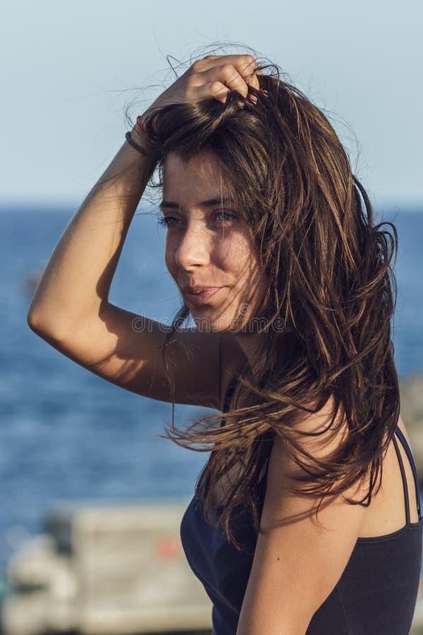 Portrait en gros plan de jeune femme bronzée gaie au-dessus de fond de bord de la mer photos libres de droits