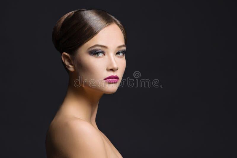 Portrait en gros plan de jeune fille de brune avec les cheveux balayés, égalisant le maquillage, les épaules nues et le long cou  images libres de droits