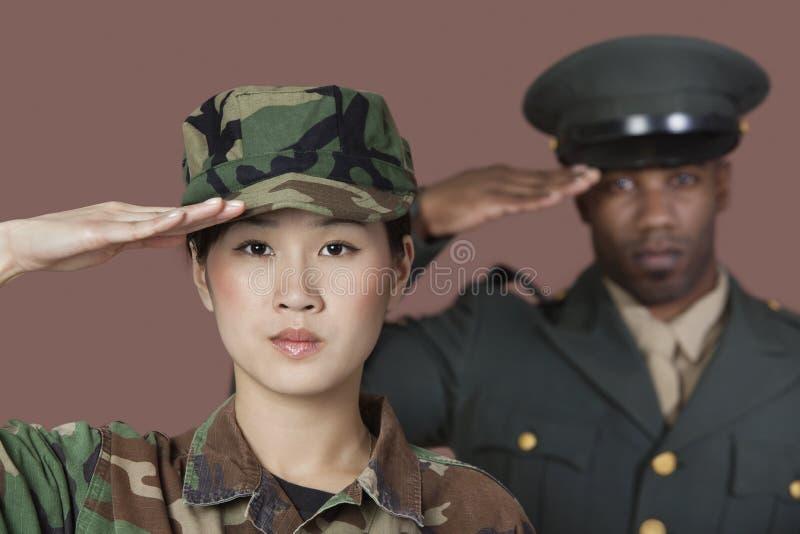 Portrait en gros plan de jeune soldat des USA Marine Corps de femelle avec le dirigeant masculin saluant au-dessus du fond brun images stock