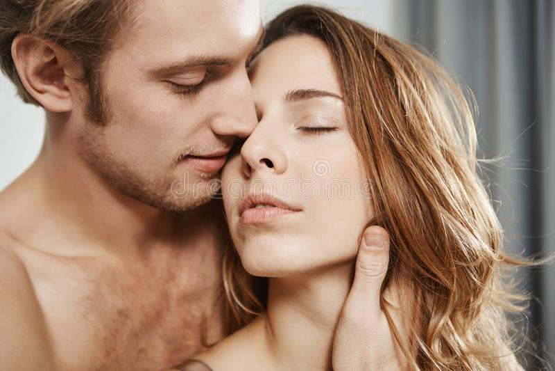 Portrait en gros plan de l'ami affectueux bel tenant la femme derrière tout en étant dans la chambre à coucher Le couple apprécie photographie stock