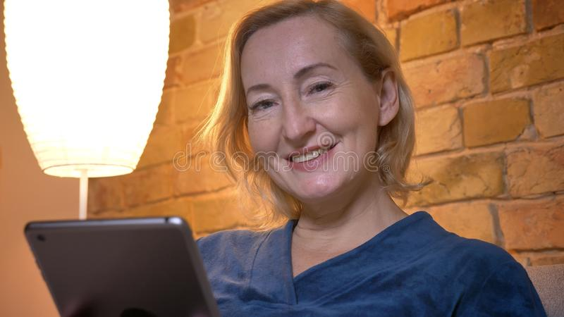 Portrait en gros plan de la dame caucasienne supérieure avec le comprimé observant avec le sourire heureux dans la caméra en atmo images stock