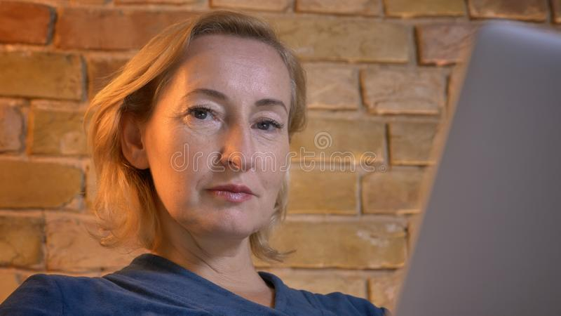 Portrait en gros plan de la dame caucasienne supérieure concentrée devant l'ordinateur portable observant sérieusement dans la ca photographie stock