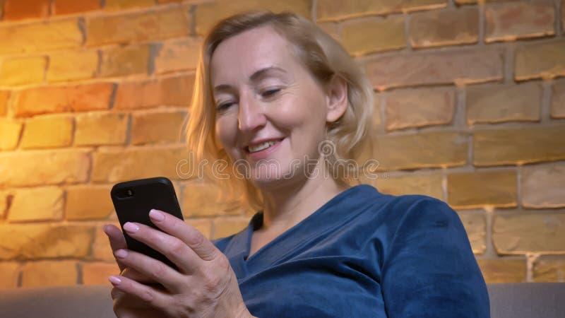 Portrait en gros plan de la dame caucasienne supérieure joyeuse s'asseyant sur le sofa et observant dans le smartphone en atmosph photographie stock libre de droits