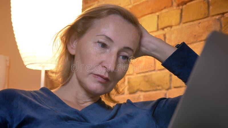 Portrait en gros plan de la dame caucasienne supérieure travaillant avec l'ordinateur portable se penchant boredly en main en atm photographie stock libre de droits