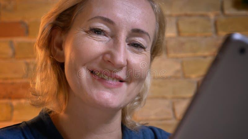 Portrait en gros plan de la dame caucasienne supérieure travaillant avec le comprimé et observant dans la caméra smilingly dans l image libre de droits