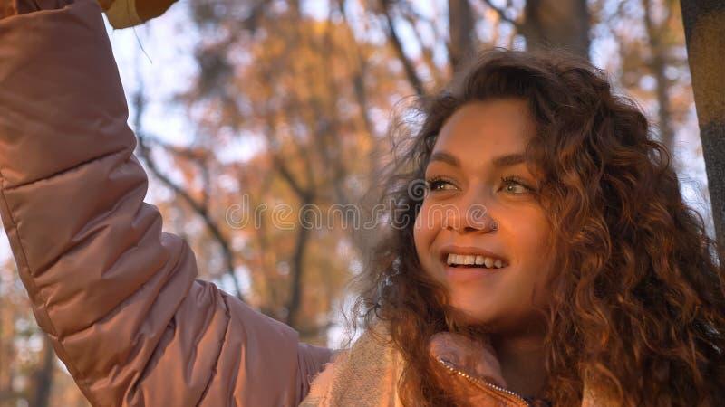Portrait en gros plan de la fille caucasienne aux cheveux bouclés de sourire touchant des feuilles sur des arbres en parc automna images libres de droits