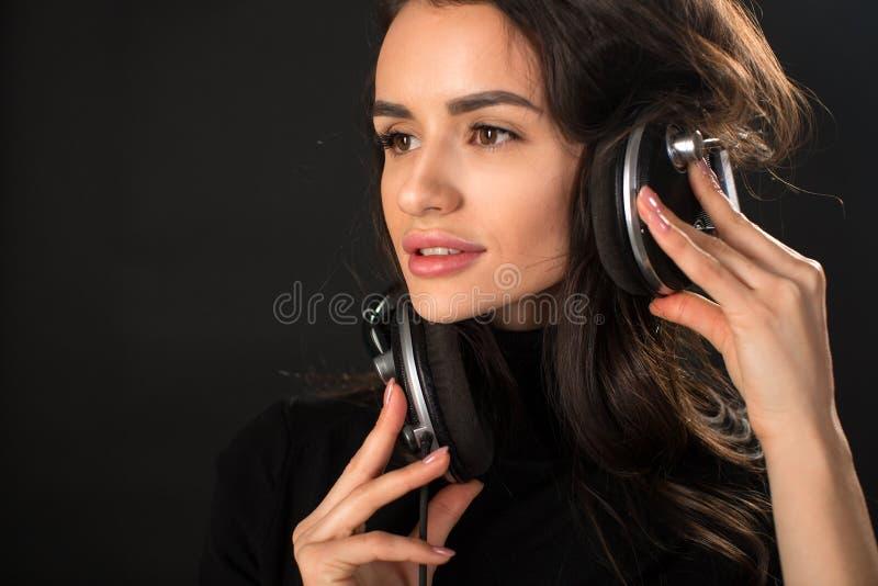Portrait en gros plan de la jeune belle femme de brune écoutant la musique et tenant des écouteurs au-dessus de fond gris-foncé images stock