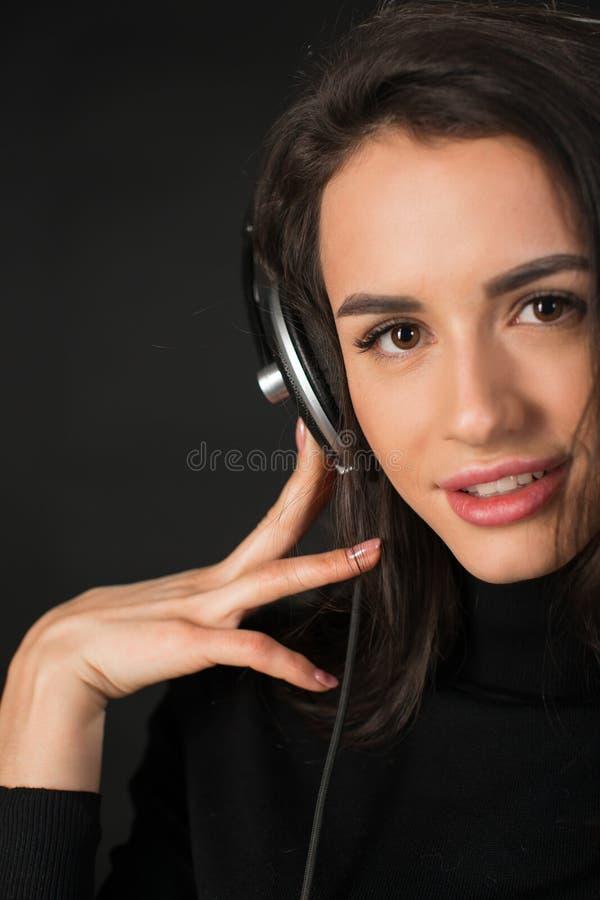 Portrait en gros plan de la jeune belle femme de brune écoutant la musique et tenant des écouteurs au-dessus de fond gris-foncé photos libres de droits