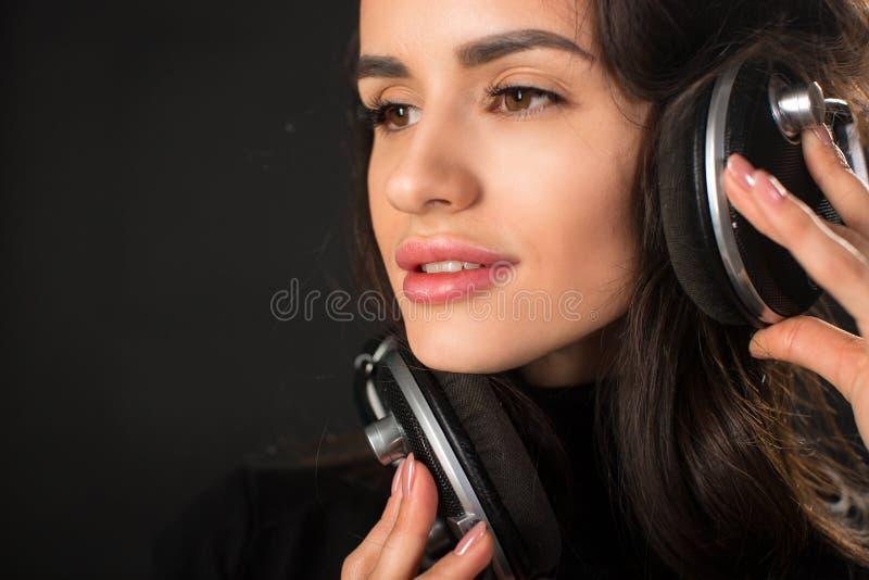 Portrait en gros plan de la jeune belle femme de brune écoutant la musique et tenant des écouteurs au-dessus de fond gris-foncé images libres de droits