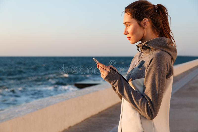 Portrait en gros plan de la jeune belle femme de sport tenant le smartph photo stock