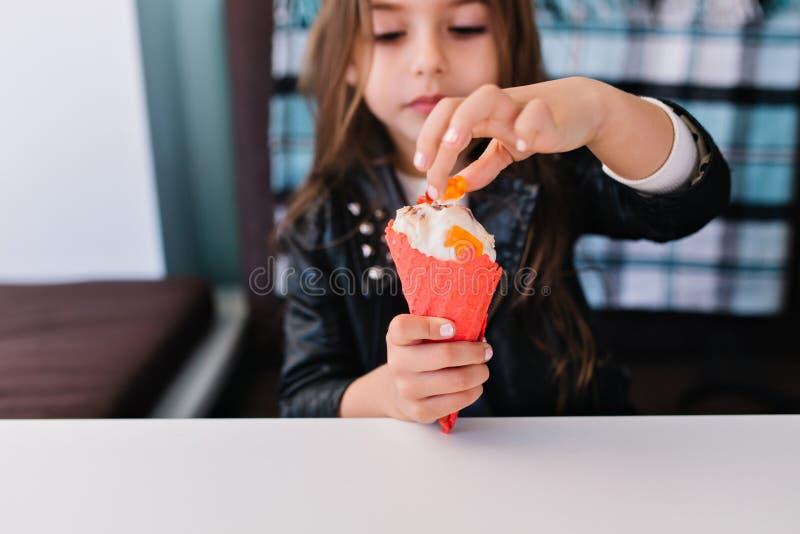 Portrait en gros plan de petite fille de charme de brune avec la manucure blanche touchant son dessert froid savoureux Enfant mig photos libres de droits
