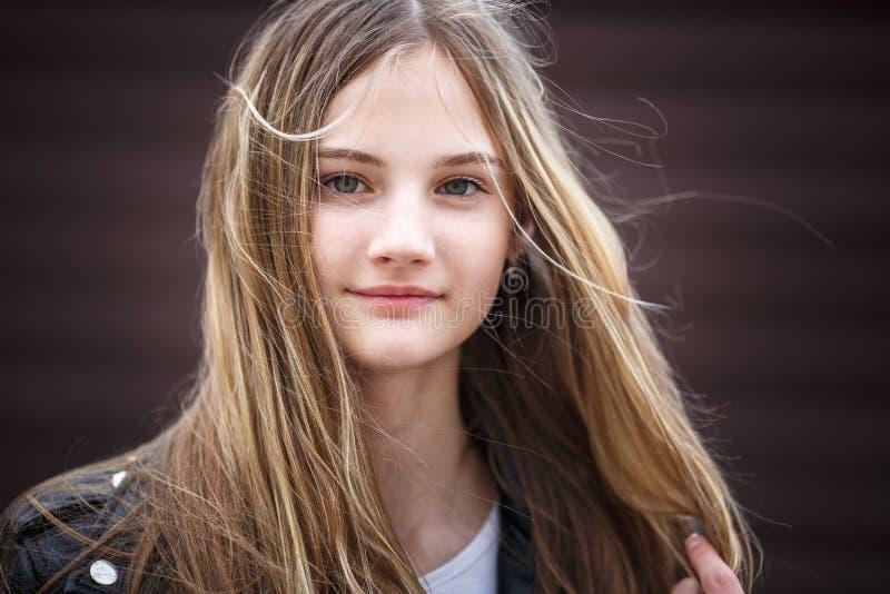Portrait en gros plan de peu de belle fille élégante d'enfant avec les cheveux longtemps débordants contre un mur rayé brun photographie stock