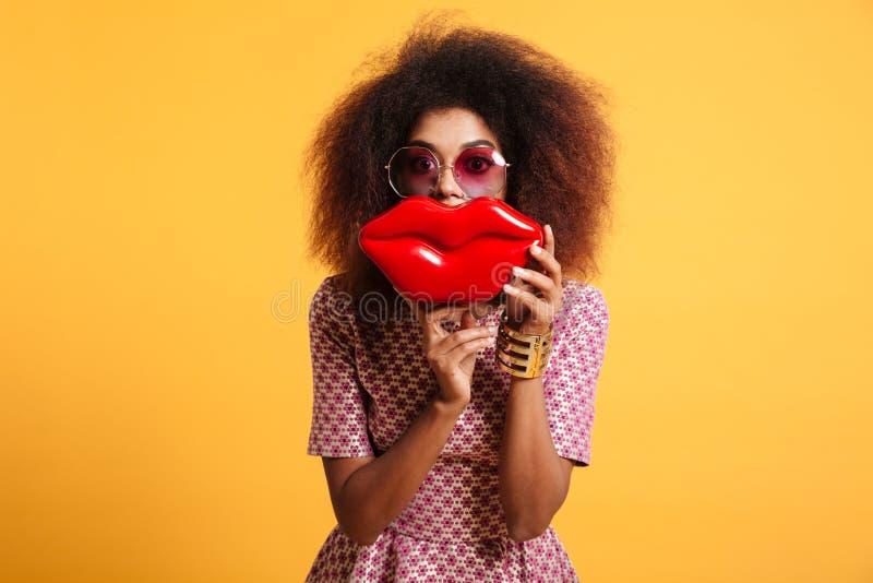 Portrait en gros plan de wooman africain espiègle dans le holdin de lunettes de soleil image stock