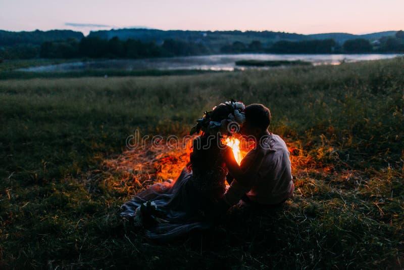Portrait en gros plan des couples heureux reposant de retour l'embrassement par le feu la nuit Fille en guirlande image stock