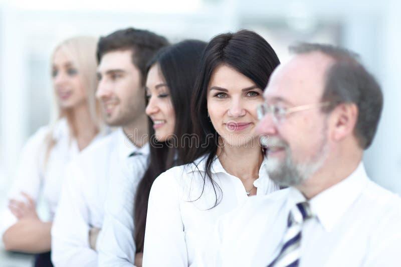 Portrait en gros plan des gens d'affaires ex?cutifs se tenant dans une rang?e au bureau et regardant l'appareil-photo photographie stock libre de droits