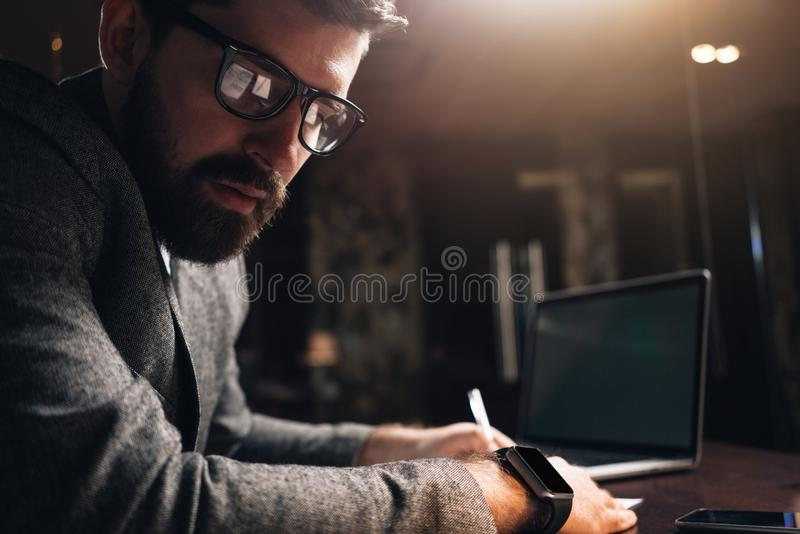 Portrait en gros plan des verres et du smartwatch de port d'oeil d'homme barbu à l'espace coworking de grenier de nuit Jeune rega photos libres de droits