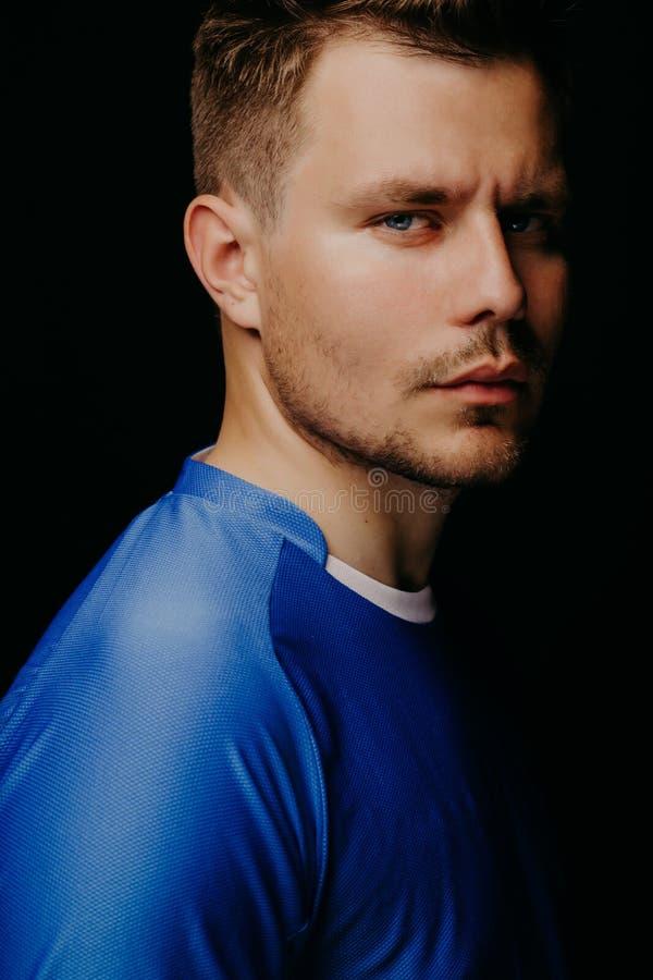 Portrait en gros plan du jeune football beau de joueur de football posant sur le fond foncé noir photographie stock libre de droits