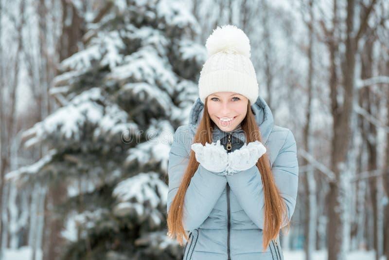 Portrait en gros plan extérieur de jeune belle fille de sourire heureuse, de chapeau tricoté élégant de port et de gants d'hiver  image stock