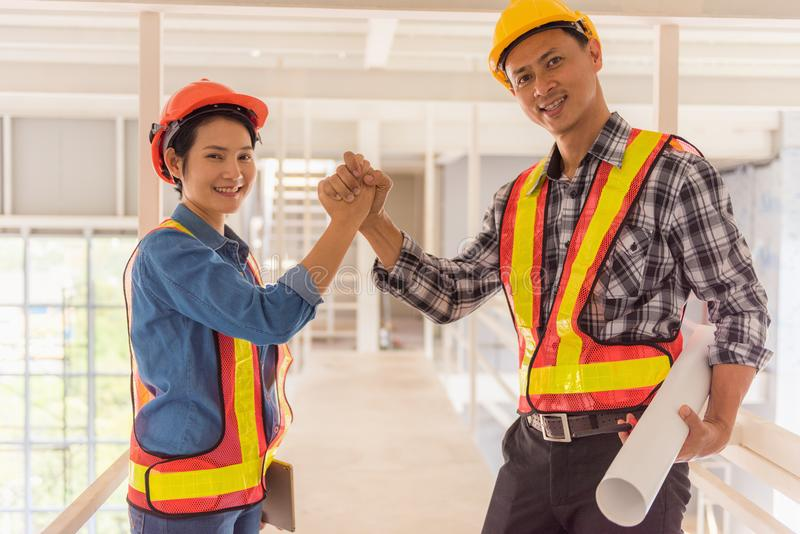 Portrait of engineer and architect jointing hands teamwork royalty free stock photography