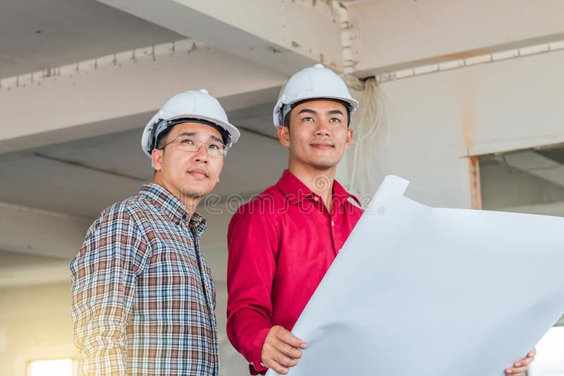 Portrait of engineer checking the blueprint and talking about construction project with commitment to success at construction site royalty free stock photos