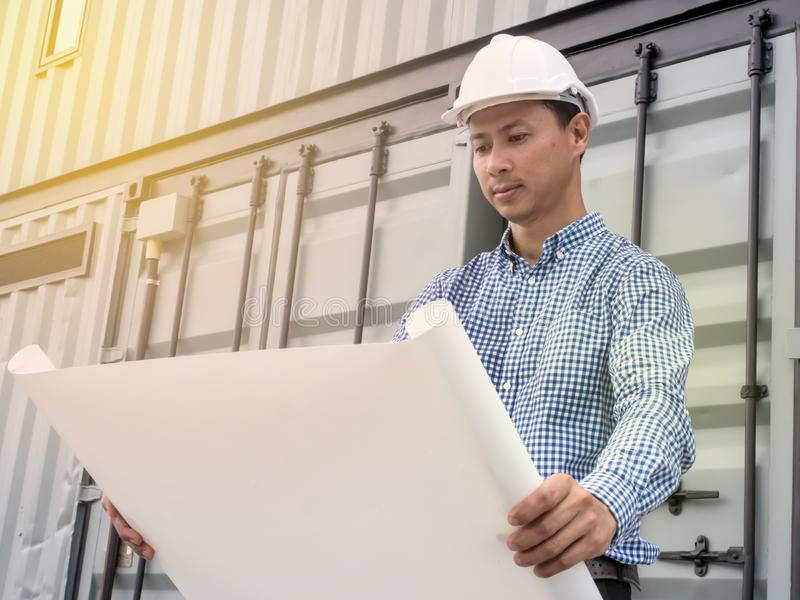 Portrait of an engineer man with helmet looking paper plans at construction site, Project engineer royalty free stock photography