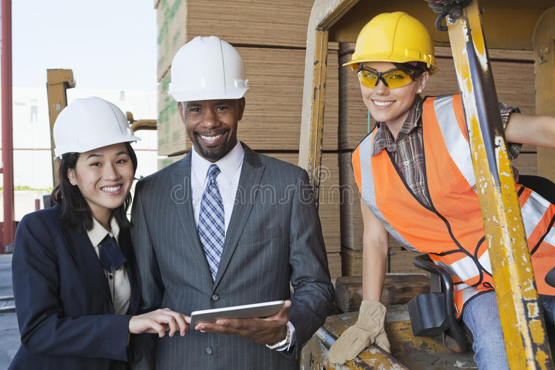 Portrait of engineers and female industrial worker smiling royalty free stock photo