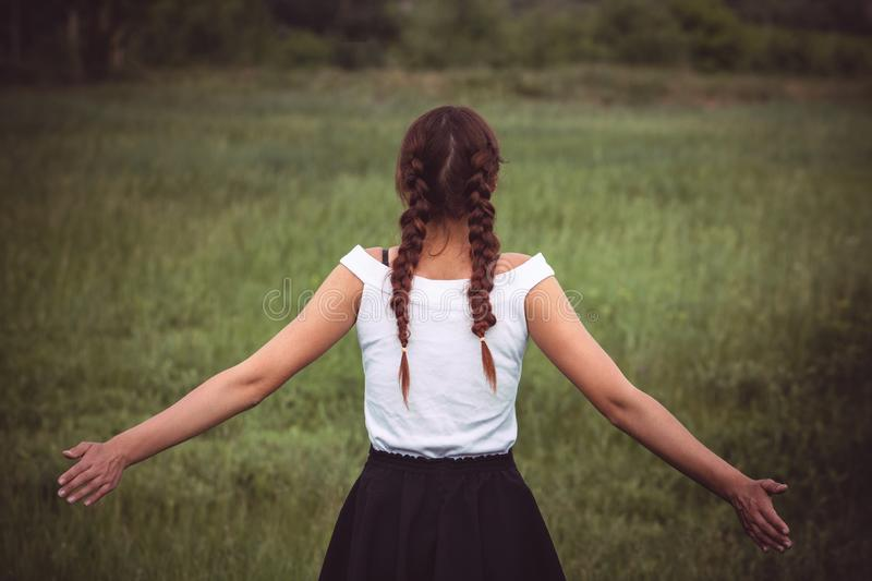 Portrait of enjoying woman raising her hands in the field royalty free stock image