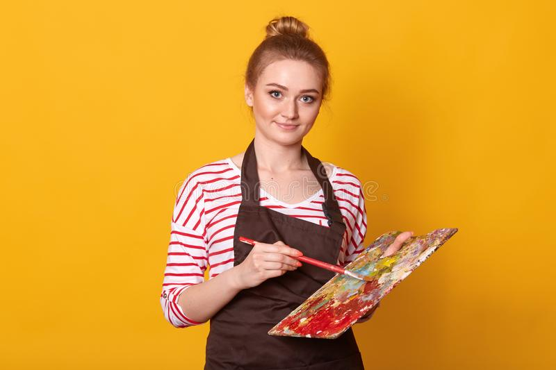 Portrait of enrgetic creative painter holding palette, making sweeping brushstrokes with equipment, looking directly at camera, royalty free stock photo