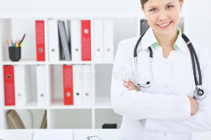Portrait of an enthusiastic female medical intern with crossed hands looking at camera. stock photography
