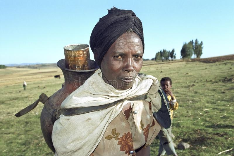 Portrait of Ethiopian woman lugging drinking water stock image