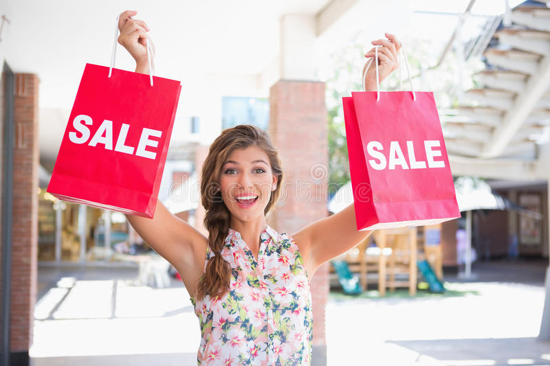 Portrait of euphoric woman holding two sale shopping bags royalty free stock image