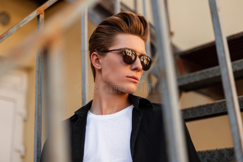Portrait of a European serious young man with a fashionable hairstyle in stylish clothes in trendy sunglasses. Handsome guy. Hipster is sitting on a vintage royalty free stock image