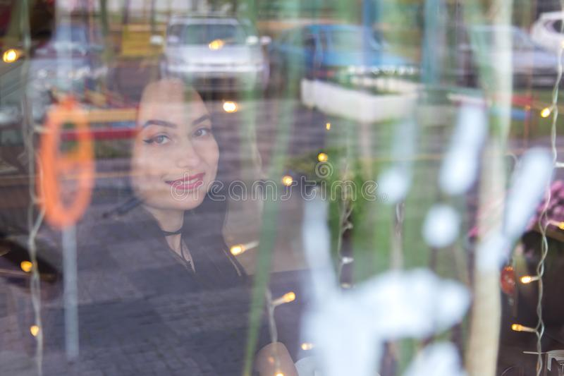 Portrait of a European woman sitting in cafe looking out the window. Shot through the window. Portrait of a European woman sitting in a cafe looking out the stock image
