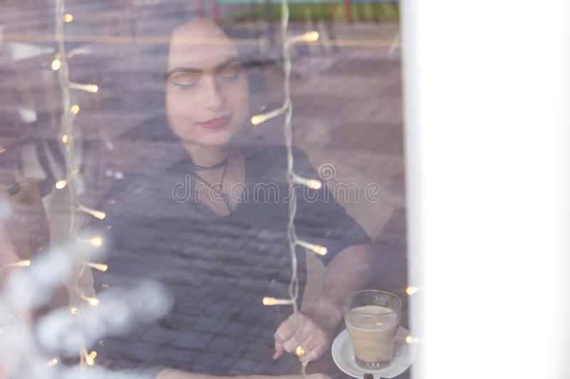 Portrait of a European woman sitting in cafe. Shot through the window. Portrait of a European woman sitting in a cafe. Shot through the window royalty free stock photo
