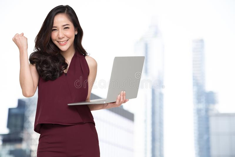 Portrait of an excited Asian woman holding laptop computer and celebrating success over building background, Raising arms with a royalty free stock images