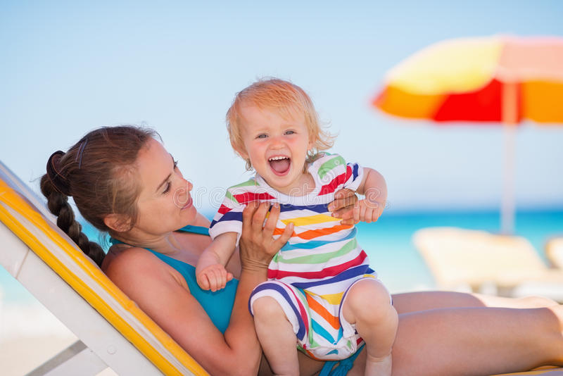 Portrait of excited baby with mother on beach. Portrait of excited baby girl with young mother on beach royalty free stock photos