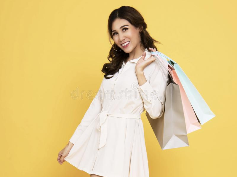 Portrait of an excited beautiful asian girl wearing dress holding shopping bags isolated on yellow background stock photo