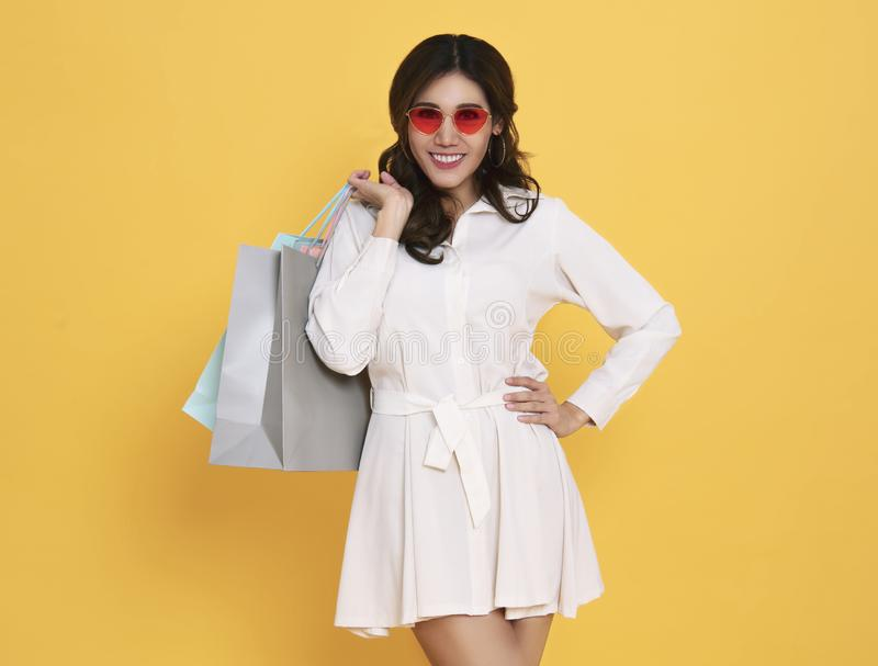 Portrait of an excited beautiful asian girl wearing dress and sunglasses holding shopping bags isolated on yellow background royalty free stock image