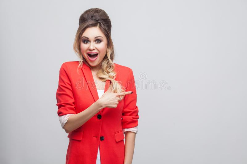 Portrait of excited beautiful business lady with hairstyle, makeup in red fancy blazer standing, looking at camera and pointing at. Copyspace and surprised stock photo