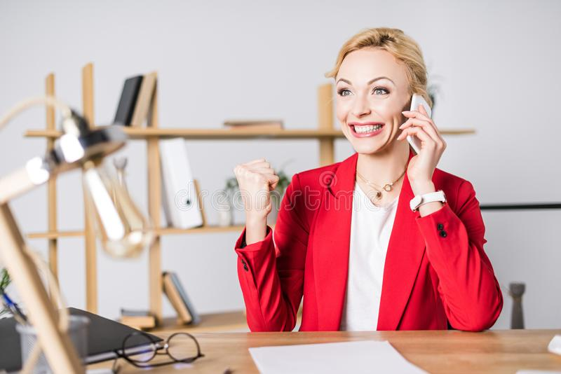 portrait of excited businesswoman talking on smartphone at workplace royalty free stock photography